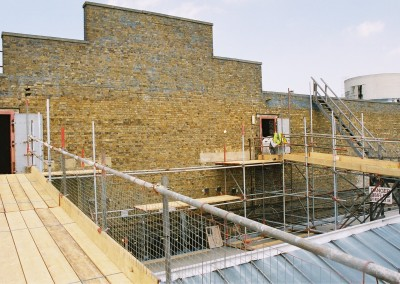 Scaffold walkway installed to remove reinforced concrete walls in atrium