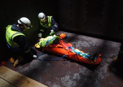 Injured person being secured into rescue stretcher for confined space rescue