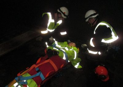 Injured person secured into rescue stretcher for confined space rescue